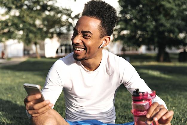 L'uomo di buon umore riccio dalla pelle scura in maglietta bianca a maniche lunghe e pantaloncini blu ride sinceramente, tiene il telefono e una bottiglia d'acqua rosa nel parco