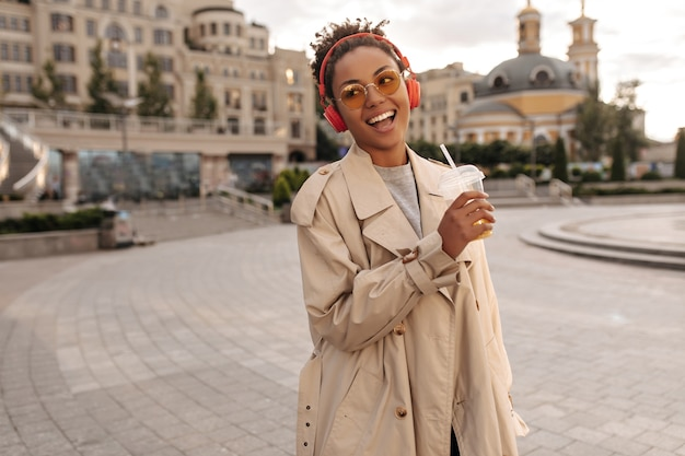 Good-humored woman in beige oversized trench coat drinks orange juice, smiles and listens to music in red headphones outside