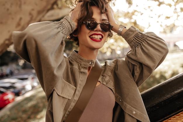 Donna di buon umore con capelli castani e labbra rosse che ride fuori. donna moderna in giacca di jeans e occhiali che sorridono all'aperto.