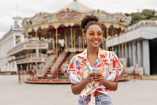 Good-humored young brunette lady in colorful summer blouse and orange sunglasses smiles, holds phone and walks outdoors