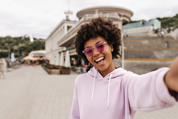 Good-humored young curly brunette woman in pink hoodie, colorful sunglasses rejoices and takes selfie outdoors
