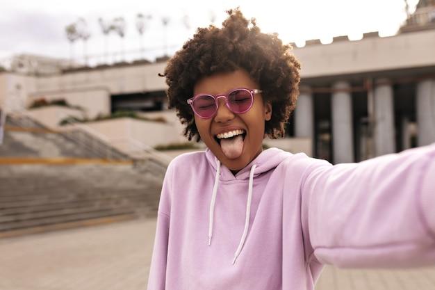 Una giovane donna riccia di buon umore con occhiali da sole rosa colorati e felpa con cappuccio viola fa una faccia buffa, mostra la lingua e si fa selfie all'esterno