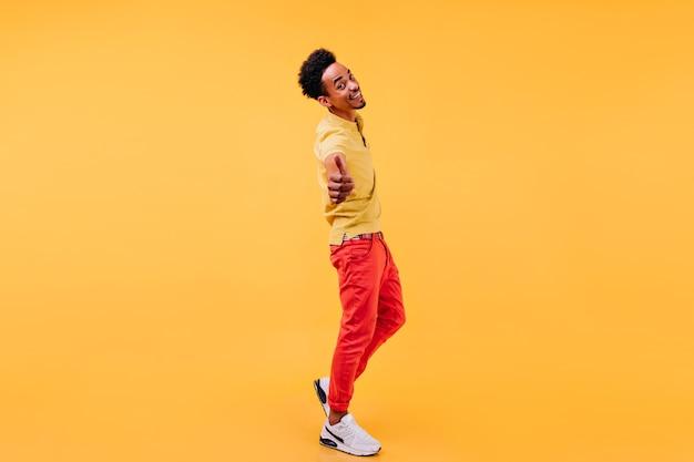 엄지 손가락으로 포즈를 취하는 빨간 바지에 착한 아프리카 남자. 트렌디 한 헤어 스타일 미소와 함께 자신감 흑인 남성 모델.