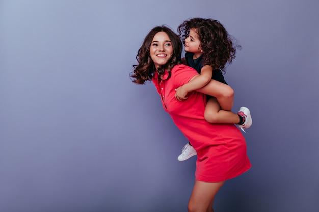 Donna caucasica di buon umore che gioca con sua figlia. ricci bruna giovane mamma divertendosi con il bambino.