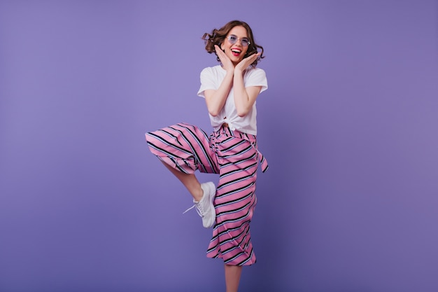 Добродушная кудрявая дама в очках, выражающая положительные эмоции. внутреннее фото стройной радостной женщины в полосатых штанах, танцующей на фиолетовой стене.