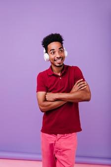 Ragazzo carino di buon umore in posa con le braccia incrociate. tiro al coperto di incredibile modello maschile ascoltando musica con sorriso sorpreso.