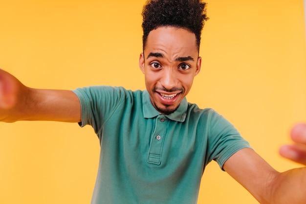 셀카를 만드는 짧은 머리를 가진 기분 좋은 검은 눈동자. 녹색 복장 포즈에 아프리카 소년의 실내 사진.