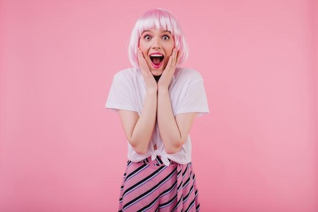気さくな女性モデルは、驚きの感情を表現するピンクのペルークを着ています。口を開けてポーズをとるかつらのかわいい白人の女の子
