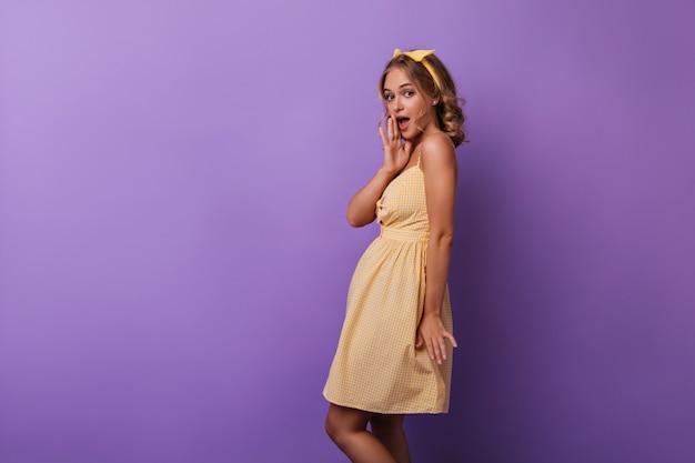Modello femminile di buon umore con pelle color bronzo che esprime stupore. ritratto dell'interno di bella donna bionda sorpresa in vestito giallo.