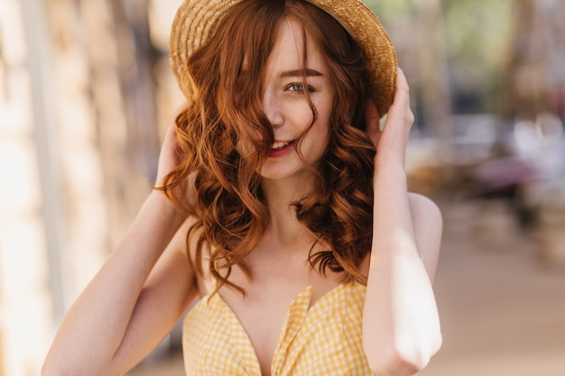 Good-humoured ginger girl in yellow clothes posing on blur street. refined red-haired woman in hat spending time in city.