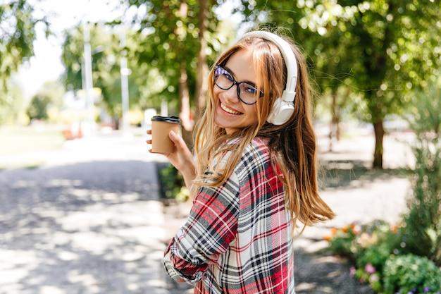 Добродушная девушка пьет кофе в парке. смеющаяся блондинка в очках, слушая музыку на природе.