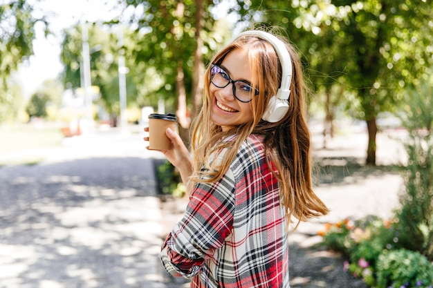 Good-humoured girl drinking coffee in park. laughing blonde woman in glasses listening music on nature.