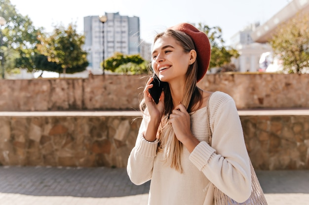 길거리에서 전화로 이야기하는 긴 머리를 가진 기분 좋은 소녀. 베레모 야외 재미에 매력적인 백인 여자.