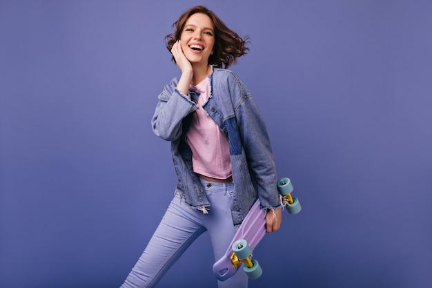 Добродушная смеющаяся женщина в джинсах танцует. фото великолепной кавказской девушки со скейтбордом.