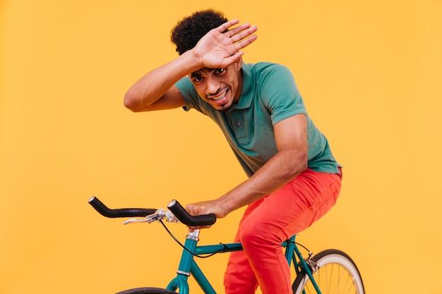자전거에 포즈를 취하는 밝은 옷을 입은 좋은 유머 남성 모델. 녹색 자전거에 앉아서 장난하는 열정적 인 흑인 젊은 남자의 실내 사진.