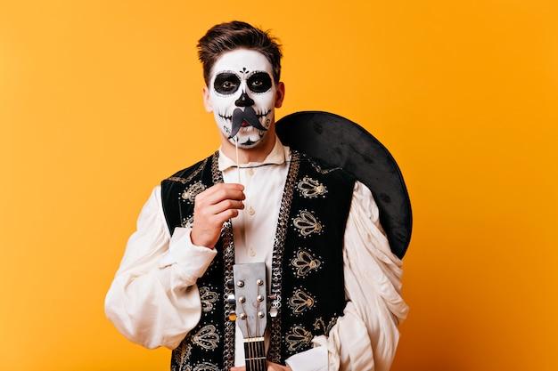 Uomo di buon umore in costume mascherato in piedi sul muro giallo. ragazzo latino in sombrero che celebra halloween.