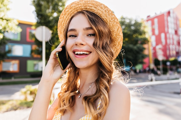 Good-humoured white girl talking on phone in summer day. outdoor portrait of spectacular lady in hat holding smartphone on street.