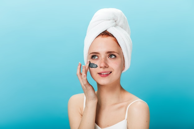 Good-humoured woman applying face mask. studio shot of cheerful girl with towel on head doing spa treatment.