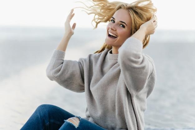 가을 주말에 바다 해안에서 즐거운 기분 좋은 여자. 자연 속에서 웃 고 백인 재미있는 여자의 야외 초상화