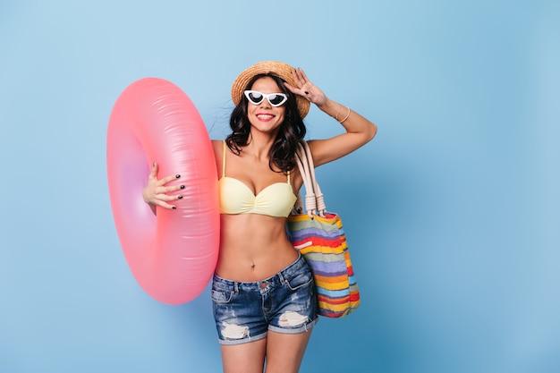 Donna di buon umore in occhiali da sole che tengono cerchio di nuoto