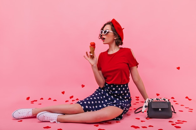 아이스크림과 함께 포즈를 취하는 흰색 덧신에 좋은 기분 어린 소녀. 베레모 바닥에 앉아 디저트를 먹는 심각한 아가씨.