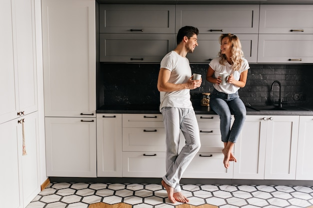 Good-humoured young man drinking tea in kitchen with stylish interior. indoor portrait of carefree couple enjoying breakfast.