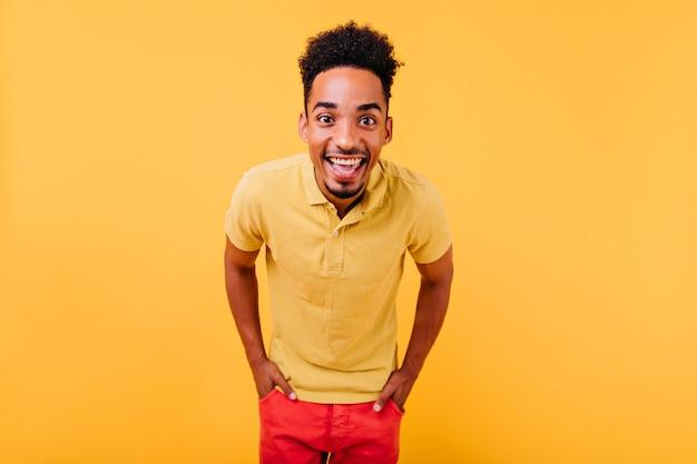 Добродушный молодой человек с темными кудрявыми волосами выражает счастье. активный африканский мальчик позирует с руками в карманах.