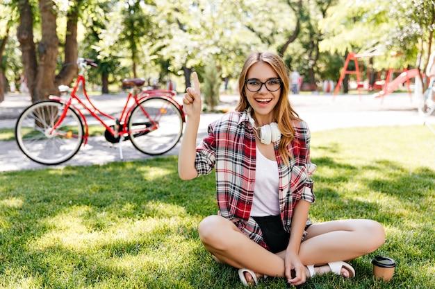 진지한 미소로 풀밭에 앉아있는 기분 좋은 젊은 여성. 공원에서 놀 아 요 blithesome 백인 여자의 야외 사진.
