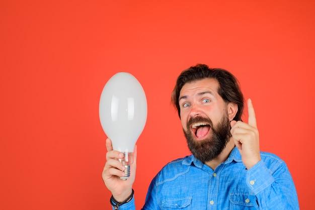 アイデアの良いアイデアの誕生ランプのアイデア電球を手に幸せな男若い男は電球を保持します