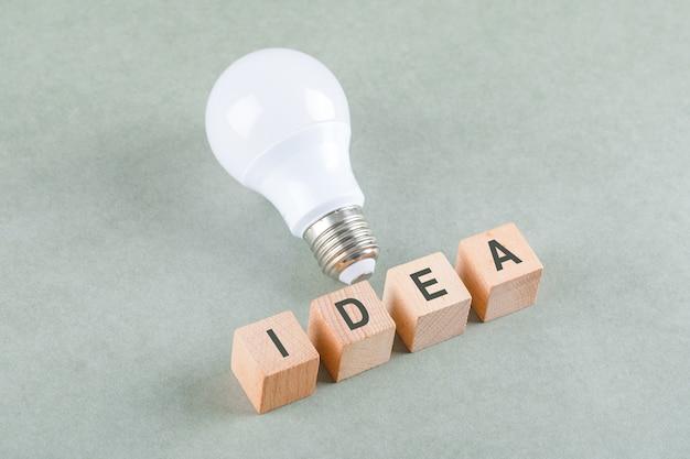 アイコンと木製のブロック、セージカラーテーブルの高角度のビューに大きな電球の良いアイデアコンセプト。