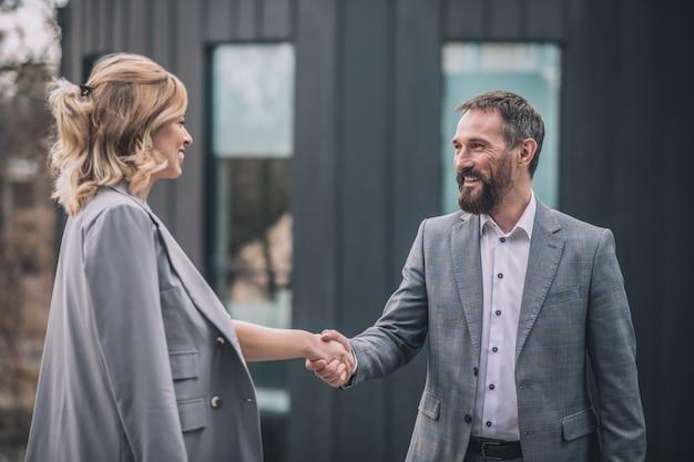 好印象。うれしそうなビジネス大人の男性と灰色のスーツを着た若いブロンドの女性がオフィスビルの近くの通りで手を振る