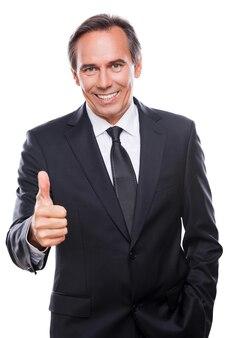 잘 했어요! 흰색 배경에 엄지손가락을 치켜들고 서 있는 동안 카메라를 보고 웃고 있는 정장 차림의 자신감 있는 성숙한 남자