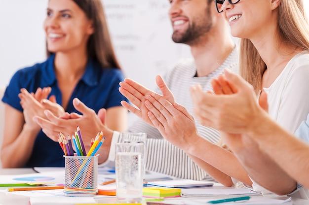 Молодец! обрезанное изображение счастливых деловых людей в элегантной повседневной одежде, сидящих за столом и аплодирующих кому-то