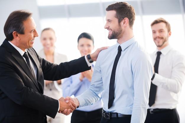 Молодец! два веселых деловых человека обмениваются рукопожатием, а их коллеги аплодируют и улыбаются на заднем плане