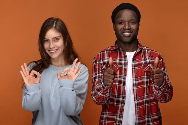 잘 했어. 잘 했어. 확인 제스처와 승인의 상징으로 엄지 손가락을 보여주는 잘 생긴 즐거운 아프리카 계 미국인 남자를 만드는 특대 운동복을 입은 행복 긍정적 인 젊은 백인 여자 등