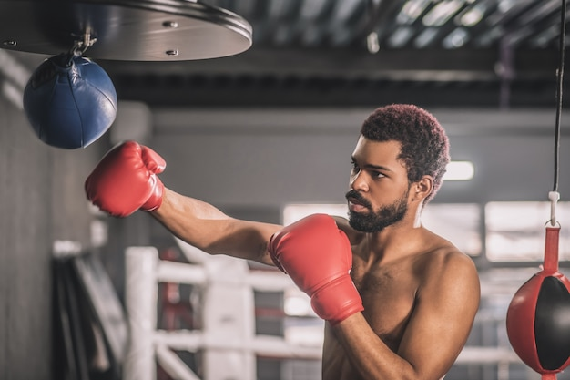 A good kick. african american kickboxer having a workout in a gym and kicking the sandbag