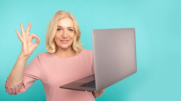 Хорошая работа ноутбука. женщина показывая одобренный знак, держащий компьютер в голубой комнате.