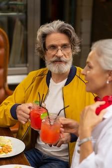 좋은 청취자. 수염 난 남자가 거리 카페에서 아내 옆에 앉아 음료수를 손에 들고 아내의 연설을 듣고 있습니다.