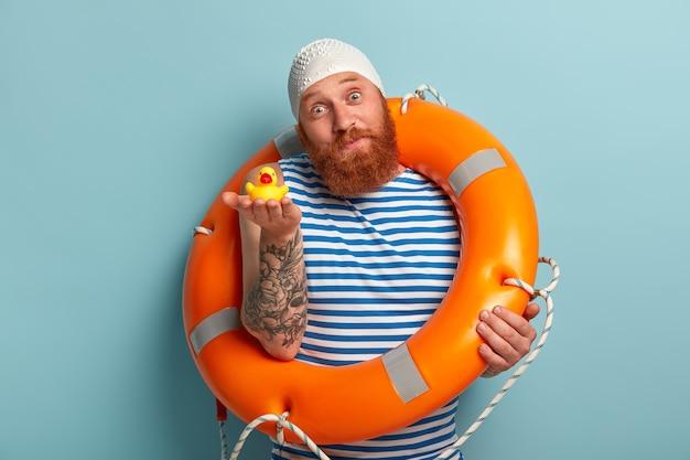 잘 생긴 활동적인 건강한 남성 수영 선수는 손바닥에 노란색 고무 오리를 들고 수영 장비를 사용하며 아이와 함께 수영하도록 제안합니다.