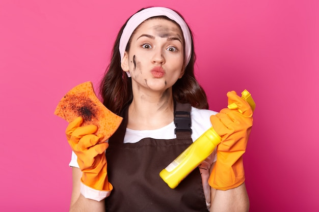 Good looking adorable woman with dirt on her face protruding her lips, holding bottle of cleaning liquid