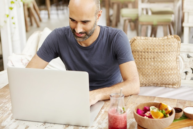 Good-looking adult man with beard checking e-mail on laptop, using free wireless internet connection at cafe, having breakfast.