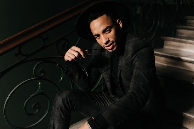 Красивый африканский мужчина сидит на лестнице и смотрит. усталый парень в куртке позирует на ступеньках.