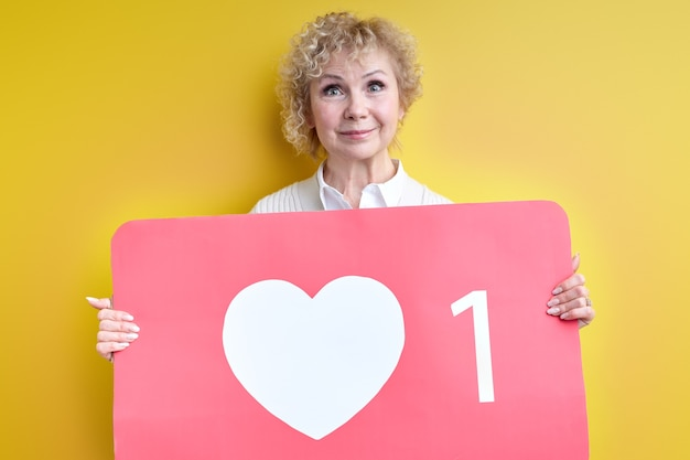 Good-looking aged woman enjoy being active in internet blogging, holding heart like sign in hands