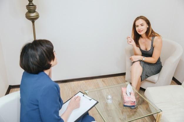 格好良い素敵な女の子がセラピストの前に座って、彼女の話を注意深く聞いています。彼女は足を組んでいます。若い女性は心理学者との会話に興味があります。
