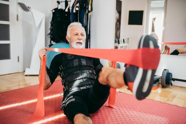 전기 근육 자극복을 입고 운동을 하는 잘생기고 긍정적인 노인.