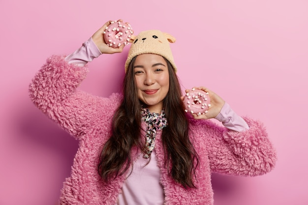 Good looking asian woman happy to forget about diet, eats sugary unhealthy food, holds donuts in hands, dances against rosy pastel space