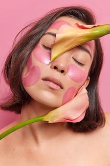 잘 생긴 아시아 여성은 얼굴 근처에 꽃을 들고 눈을 감고 셔츠를 입고 분홍색 벽에 격리된 미용 절차를 거친 피부 포즈를 새로 고치기 위해 패치를 적용합니다.