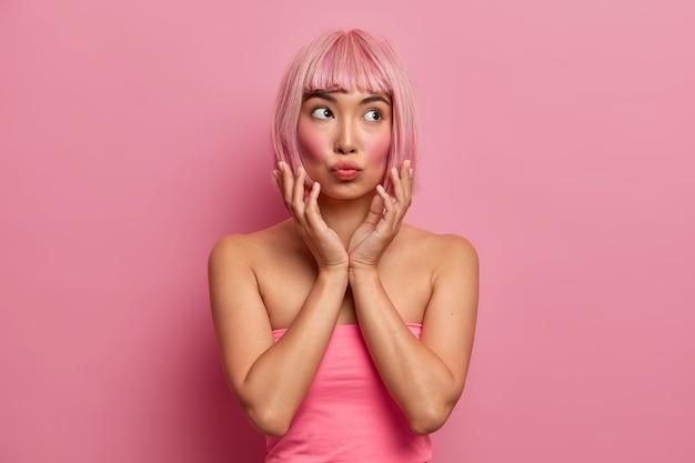 Bella donna asiatica con guance rosse, tiene le labbra piegate, mani vicino al viso, ha un'espressione pensierosa, capelli rosa, vestita in alto