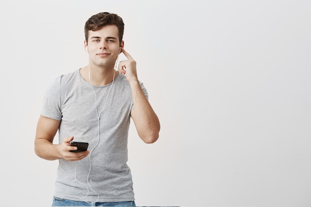 Good-looking attractive youngman in gray t-shirt having pleased look,holding mobile phone in his hand, wearing white earphones on, joyfully listens to his favourite songs, using music app.