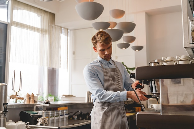 Good-looking barman in apron pouring hot beverage from the tap of coffee machine into cup